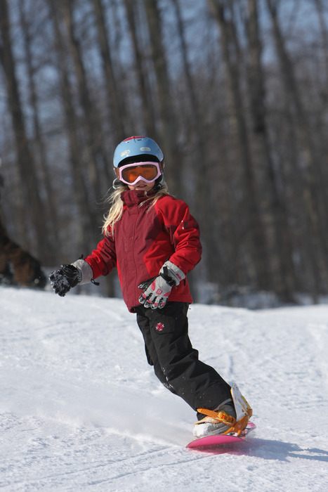 Young snowboarder makes her way down Boyne Mountain resort, Michigan