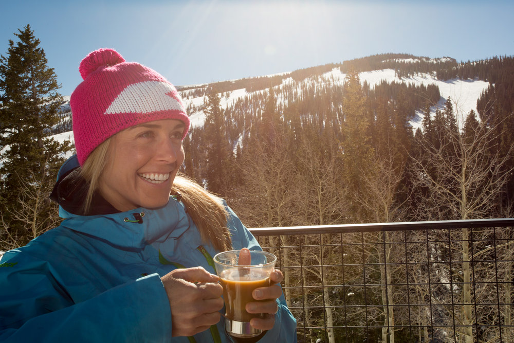 Revving up for a full day of skiing, Darcy savors a cup of joe on the deck of Sam's Smokehouse atop Snowmass Mountain.