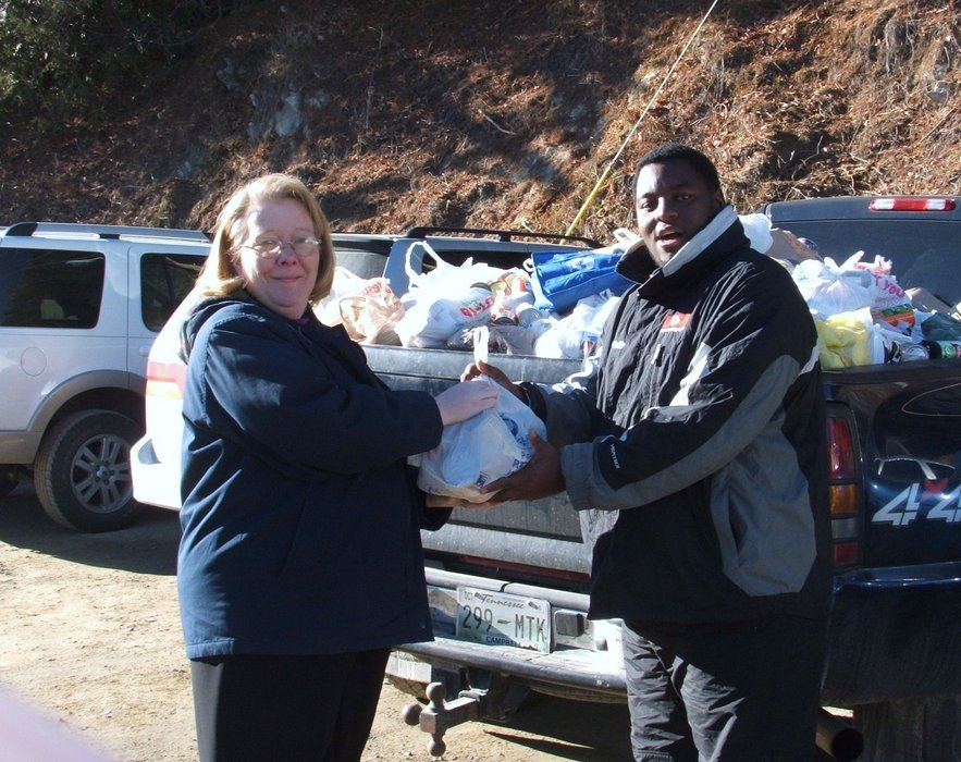 "Talmak ""Fred"" Boyd, Cataloochee Children's Program instructor assists Lisa James, Haywood Christian Ministries Director, in loading one of eight vehicles filled with donations from the Can-U-Ski canned food and coat drive at Cataloochee Ski Area on Sunday.  Over 25,000 cans of food and 300"