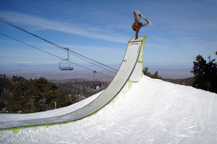 A snowboarder handplanting at Mt. High, CA.