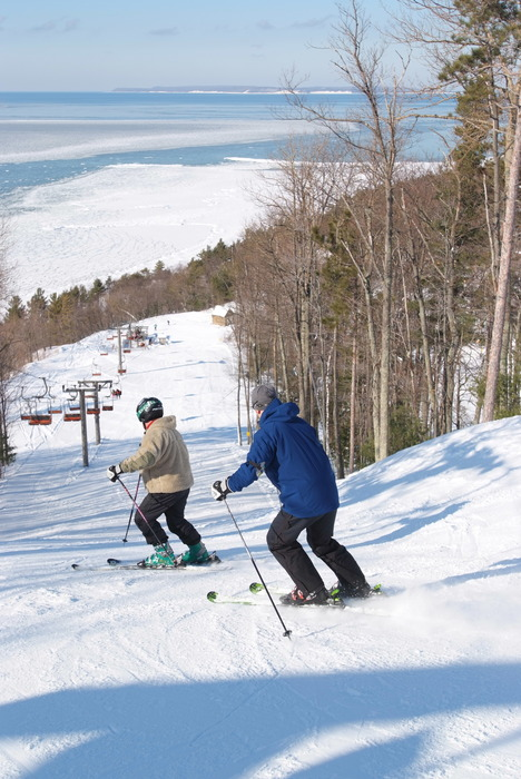 A pair of skiers heading down the slopes at Homestead, MI.