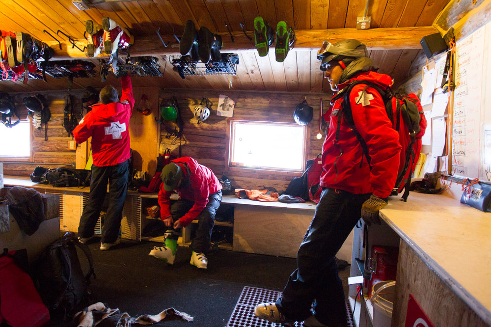 Grand Targhee ski patroller Joe Calder goes over the morning avalanche route plan as Dave Thibodeau and Lindsey Fell boot up. - ©Cody Downard Photography