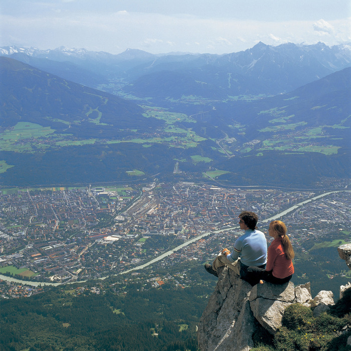 Couple sitting on rocks above Innsbruck
