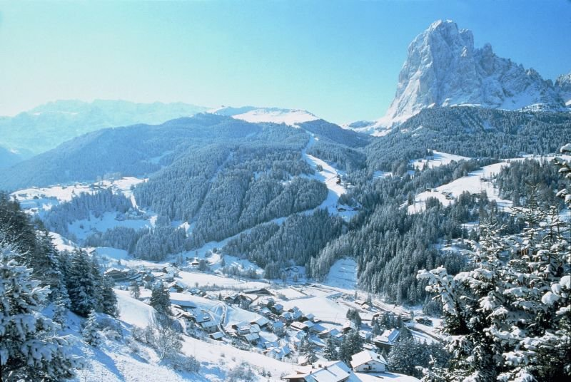 Selva Val Gardena snow-covered village through the trees