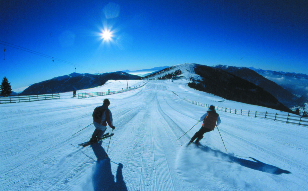 A pair of skiers on a groomed slope in Bad Kleinkirchheim