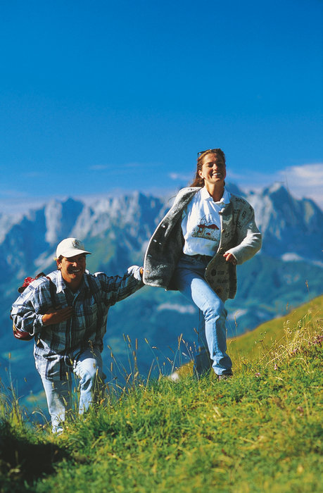 A couple hiking in the hills over Kitzbuehel, Austria.