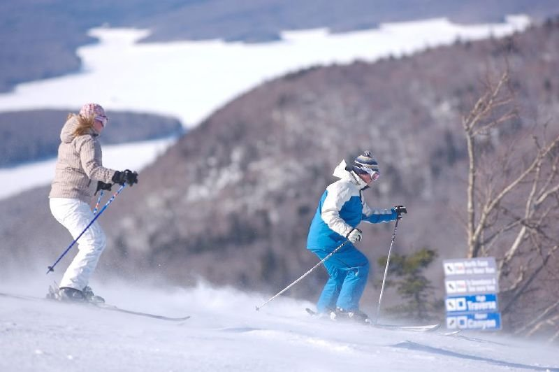 A pair of skiers stretching their legs on the wide slopes of Mt Snow, VT