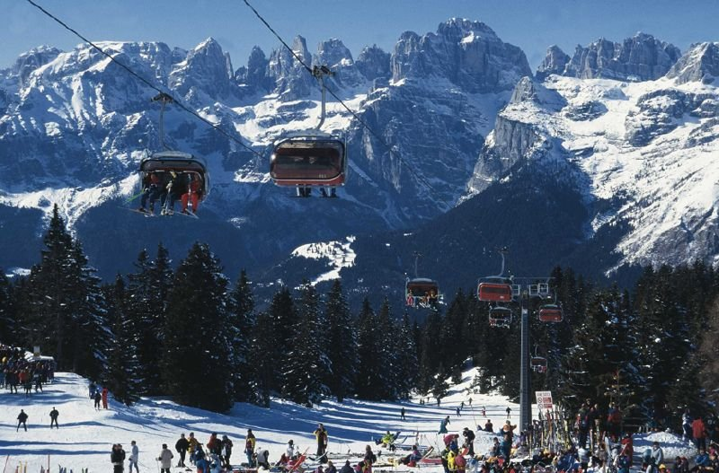 Chairlifts crossing above slopes and skiers in Andalo