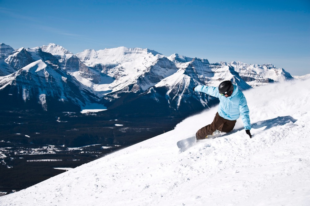 A snowboarder enjoys ripping up the slopes on a sunny day at Lake Louise Ski Area in Banff National Park. Photo Courtesy of Lake Louise Ski Area.