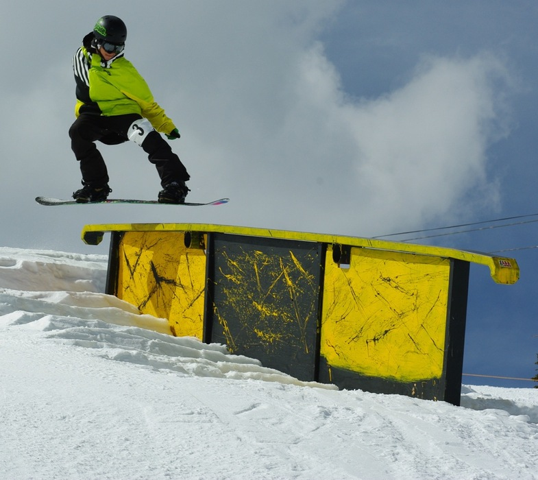 A Snowboarder catches some air on the way to a rail.