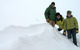 Three people hang out in the snow in Snowbird, Utah
