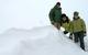 Three people hang out in the snow in Snowbird, Utah