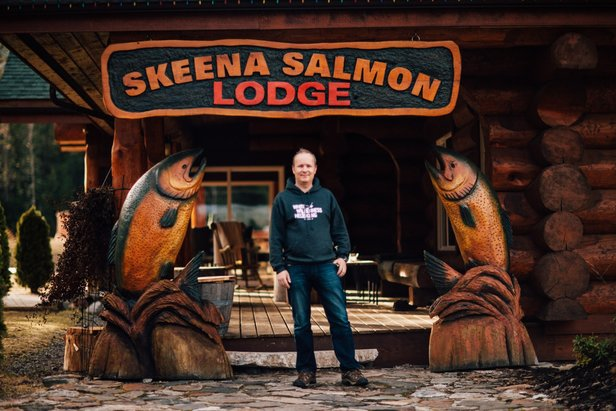 White Wilderness owner, Marcel Schneider, stands in front of the fishing lodge he renovated. Schneider's operation runs heli fishing trips in the summer and heli skiing in the winter. - ©Kyle Hamilton Photography
