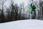 Snowboarding does a backflip at Christie Mountain. - Snowboarding does a backflip