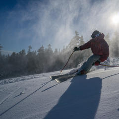 A skier carves turns under a storm of snowmaking snow at Sunday River. - ©Sunday River