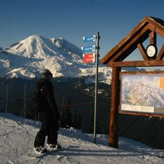 A snowboarder takes in run options overlooking Mt. Rainier at Crystal Mountain, Washington. Photo by Becky Lomax.