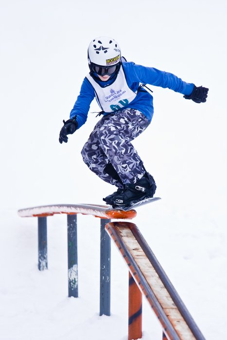 A snowboarder rides a rail in the Winter Park Resort, Coloraod terrain park