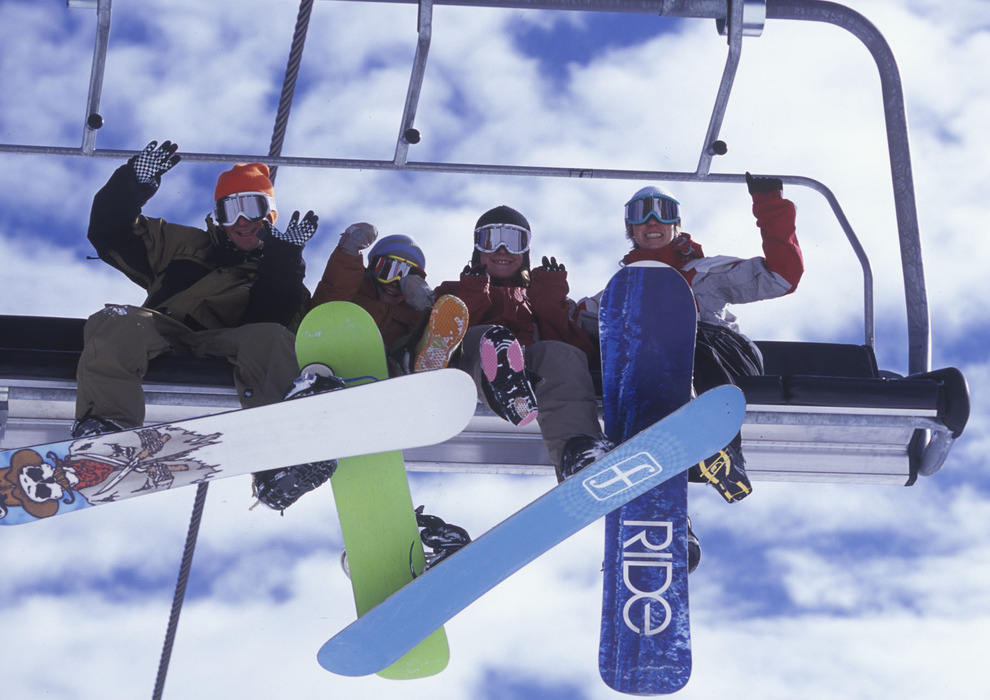 Snowboarders have fun on the chairlift in Mammoth Mountain, California