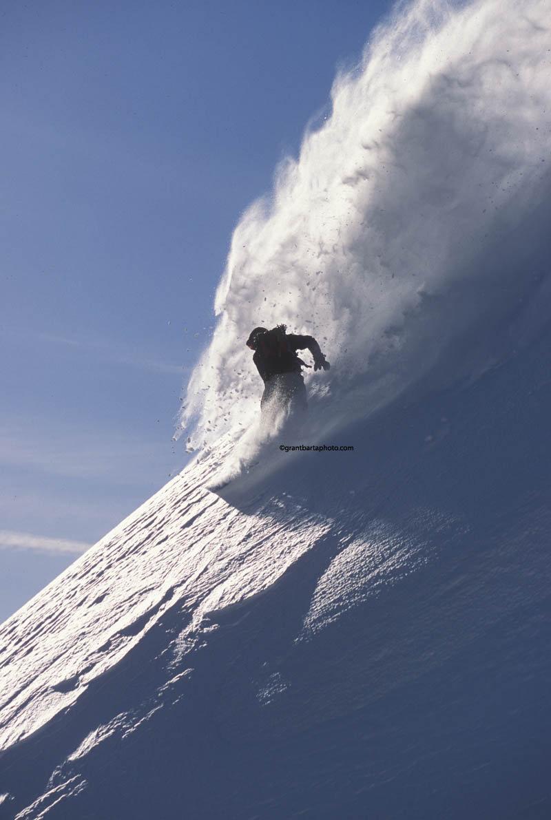 Off-piste skier on steep mountain terrain