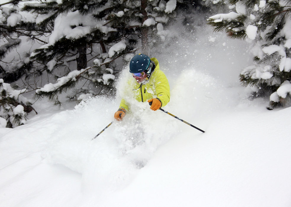 Skier crusing out of the trees and onto Basin Street slope. - ©Crystal Mountain