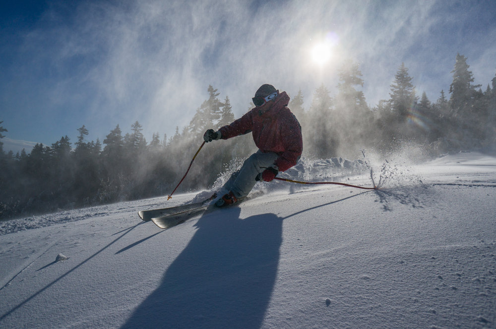 A skier carves turns under a storm of snowmaking snow at Sunday River. - © Sunday River