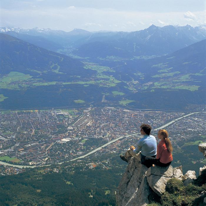 Couple sitting on rocks above Innsbruck