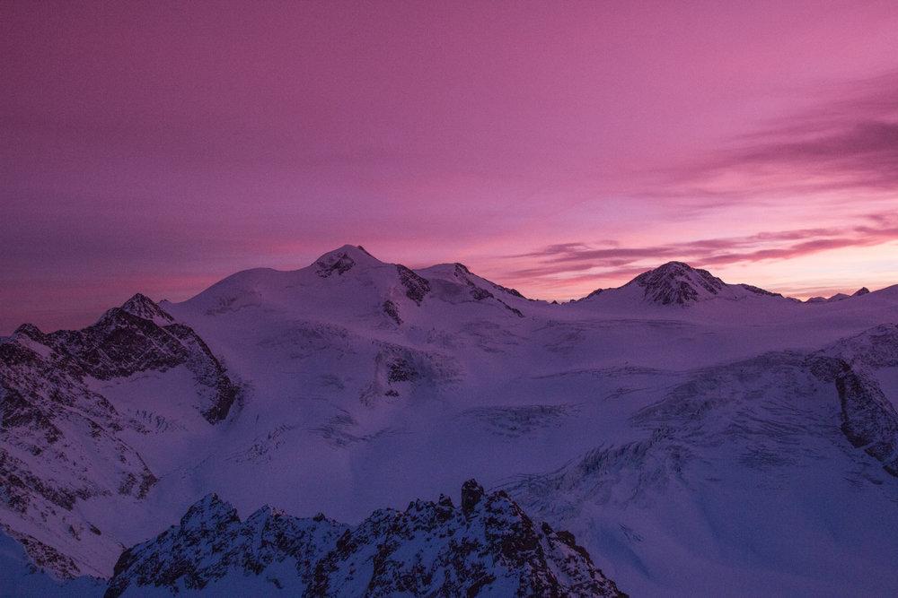 Zasnežené hory ožarujú fialové mraky - © Pitztaler Gletscherbahn