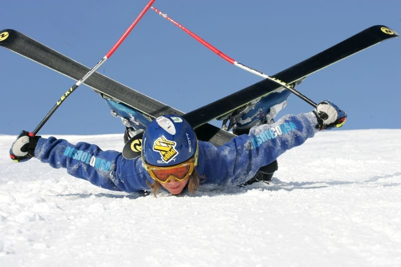 Girl lying on snow with skis crossed