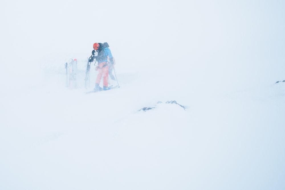 Sindre er på vei inn i nødhytten, som fremdeles er vanskelig å se selv om fotografen står kun 20 meter unna. Det kan være et kjærkomment syn om man er ute for dårlig vær.  - © Tor Berge - Norexplore