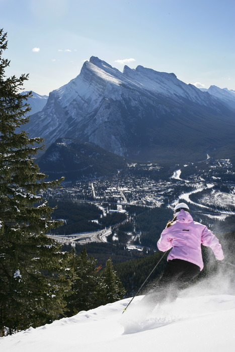 Woman skiing above Mount Norquay