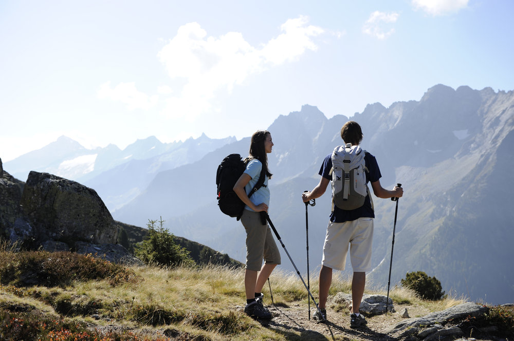 Two hikers take in remote mountain views. - © Mayrhofner Bergbahnen