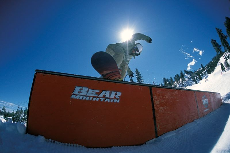 A snowboarder goes off a jump in Bear Mountain, California