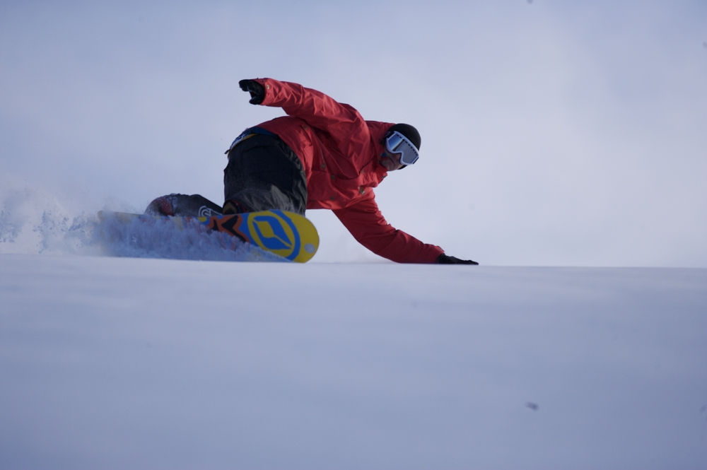 Snowboarder turning in powder