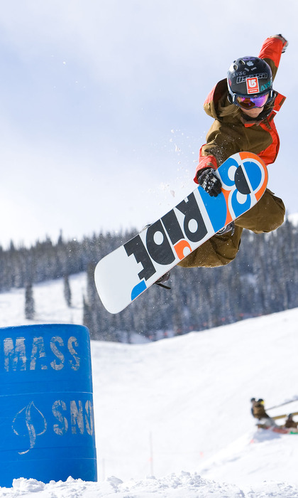 Ein junger Snowboarder jumpt im Terrain-Park in Snowmass, Colorado, in die Luft.