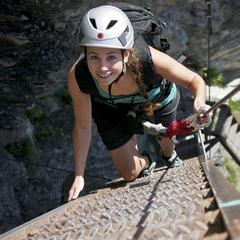 Typische Leitertechnik: Eine Hand an der Leiter, eine am Stahlseil. Impressionen aus dem Klettersteig Flims - ©Weisse Arena Gruppe